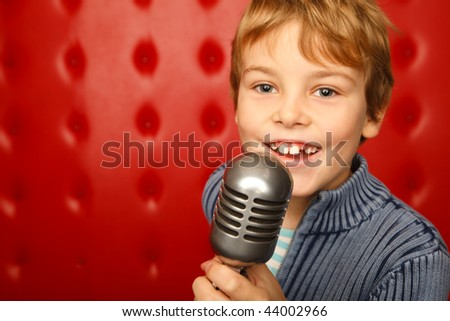 Singing boy with microphone on rack against red wall. Close up. Horizontal format. - stock photo