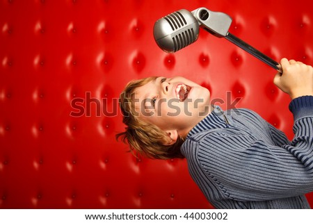 Singing boy with microphone on rack against red wall. Horizontal format. - stock photo