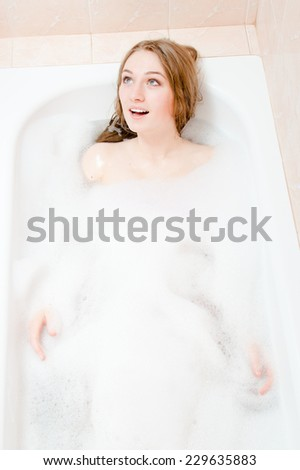 singing luxury spa: portrait of charming blonde young woman relaxing in bath with foam having fun singing, happy smiling and looking up at copy space on light background - stock photo