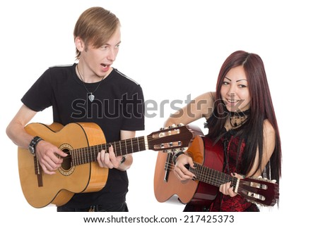 Singing musicians with guitars. Interracial young couple, Asian woman and Caucasian man. - stock photo