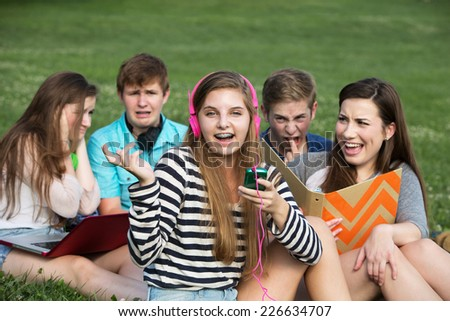 Singing teenage girl annoying friends studying outdoors - stock photo