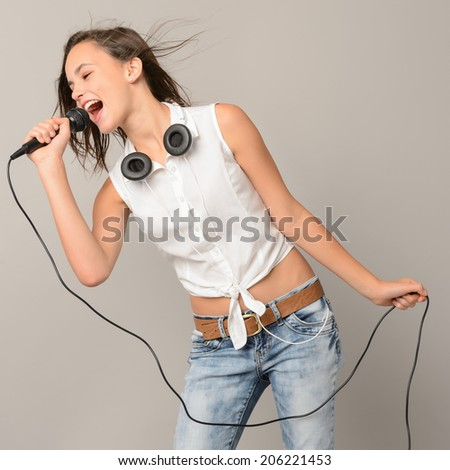 Singing teenage girl with microphone karaoke music on gray background - stock photo