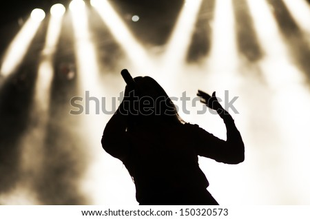 Singing woman silhouette with smoke background - stock photo