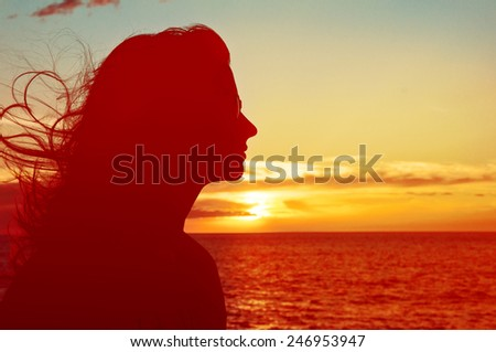 Single adult woman silhouette with sunglasses at Pacific ocean Sunset with flying hair - stock photo