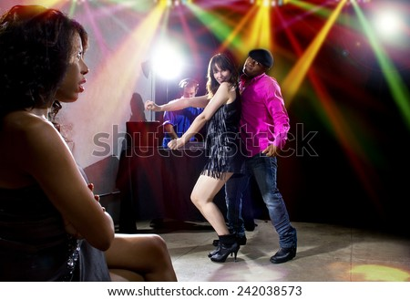 single black woman jealous of interracial couple on dancefloor - stock photo