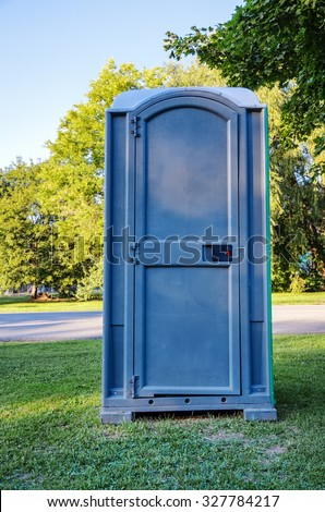 Single Blue Outhouse on Grass for Public Use - stock photo
