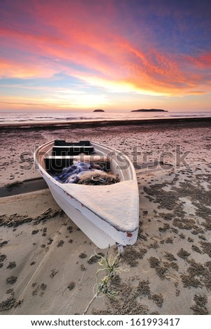 SIngle boat at sunset - stock photo