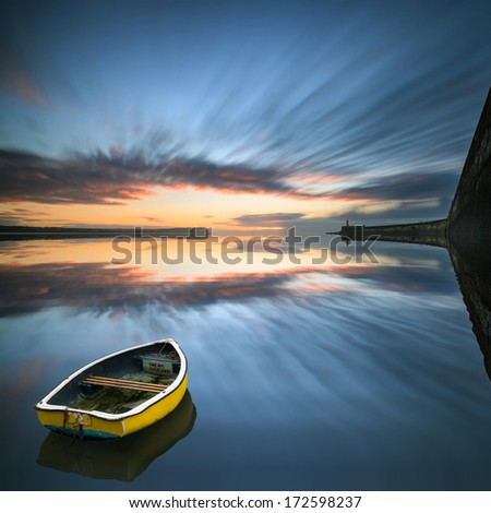 Single boat floating no water during sunrise over ocean with lighthouse and harbor wall - stock photo