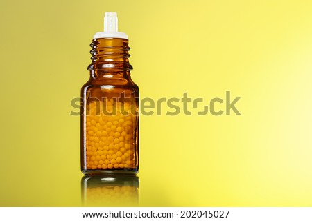 single bottle with homeopathy globules with yellow background. - stock photo