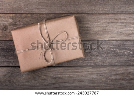 Single brown package tied with string on a wood background - stock photo