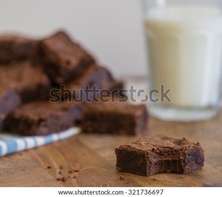 Single brownie with bite in foreground, with pile of brownies on napkin and milk in background in vintage style on old wood surface - stock photo