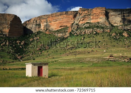 Single building against a mountain backdrop in the Golden Gate National Park in the northern part of the Drakensberg Mountain range of South Africa - stock photo