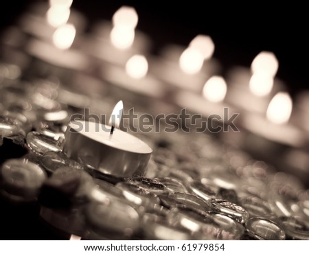 Single Candle Focus on Glass Beads in Aged Film Effect - stock photo