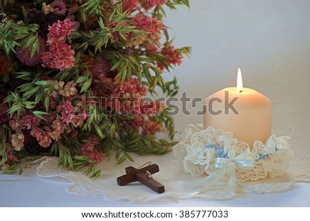 Single candle in a wedding garter with a bouquet of dried flowers and a wooden catholic cross on festive embroidered white tablecloth - stock photo
