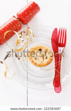 Single Christmas fruit mince pie in a crystal plate and red Christmas tableware over rustic wooden background - stock photo