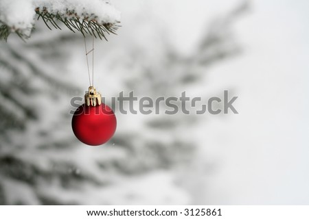 single Christmas ornament hanging on a tree outside in the snow - stock photo