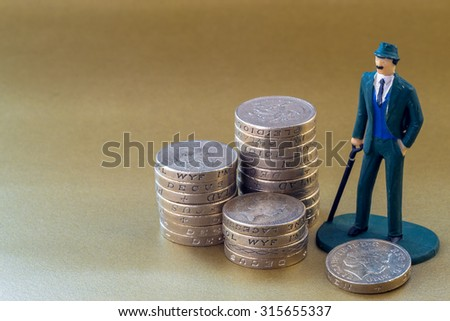 Single classical businessman miniature toy in suit and tie on a golden background with copy space surrounded by English one pound coins - stock photo