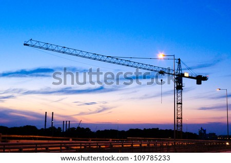 Single crane at night on construction site - stock photo