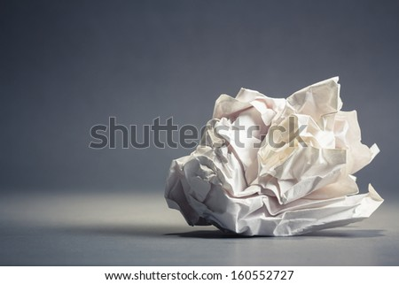 Single crumble paper ball on gray ground with copy space - stock photo