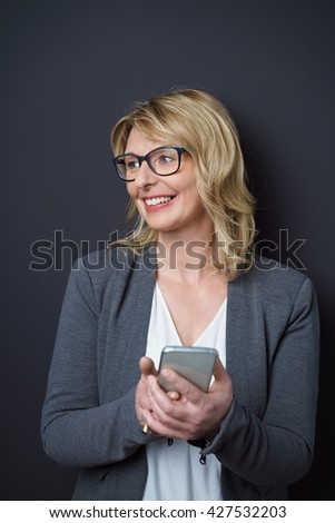 Single cute business woman in gray blazer over white blouse with digital device in hand while looking sideways - stock photo