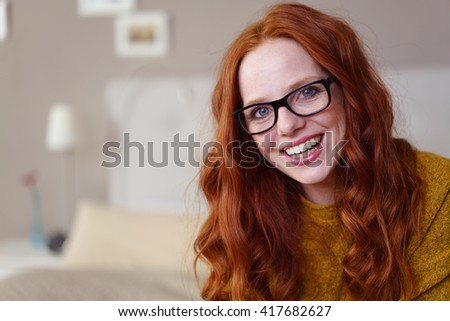 Single cute laughing red headed female in eyeglasses and yellow sweater sitting on bed laughing next to copy space - stock photo