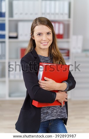 Single cute smiling office worker in jacket, sweater and jeans holding large red binder in front of bookshelf indoors - stock photo