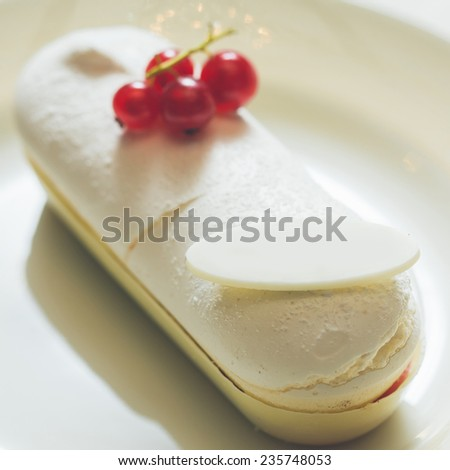 Single eclair with space for text on white plate. Warm colors. Shallow dof.  - stock photo