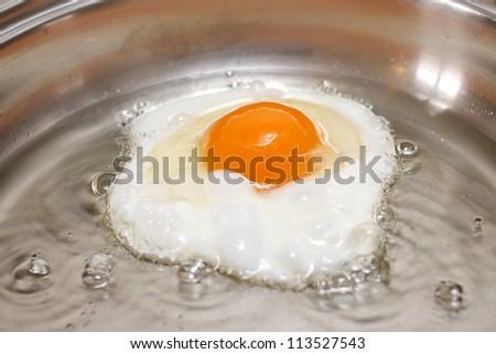 Single egg frying in a metal pan - stock photo