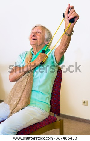 Single elderly woman in chair using elastic stretching bands to strengthen her shoulders and arms - stock photo