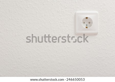 Single empty electric socket on white wall - stock photo