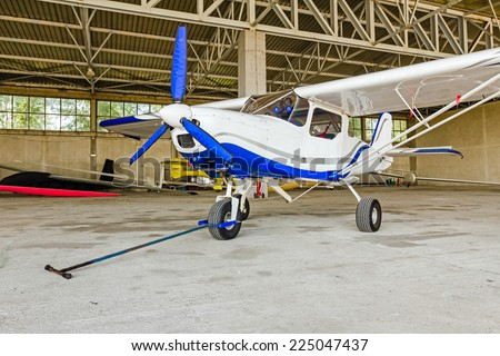 Single engine aircraft ready for pulling out with a tow bar from hangar - stock photo