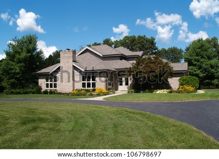 Single family brick contemporary home with a circle drive. - stock photo