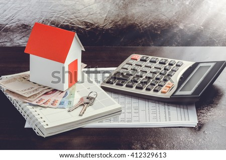 Single family house on pile of money. Concept of real estate. - stock photo