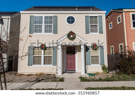 Single family house with two levels and a sidewalk. - stock photo