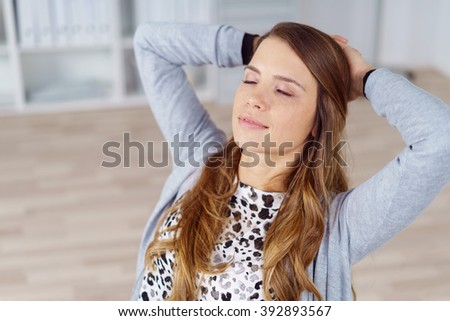 Single female office worker in long brown hair and gray sweater with eyes closed while leaning back in chair with hands behind her head - stock photo