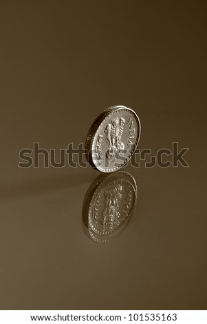 Single five rupee Indian coin and its reflection - stock photo
