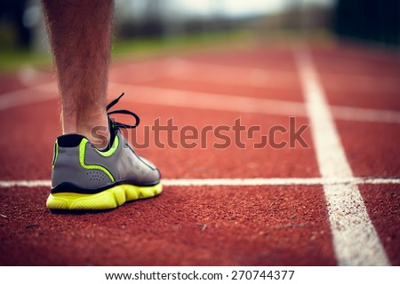 Single foot at the start of track - stock photo