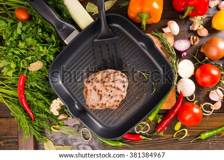 Single fried pork chop and black spatula in middle of pan surrounded by colorful fresh vegetables and herbs over wooden table - stock photo