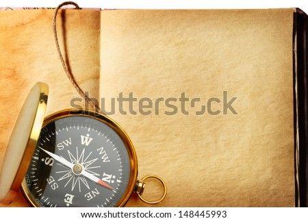 Single golden compass on book background  - stock photo