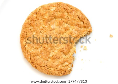 Single golden oat biscuit with a bite missing. Shot from above - stock photo