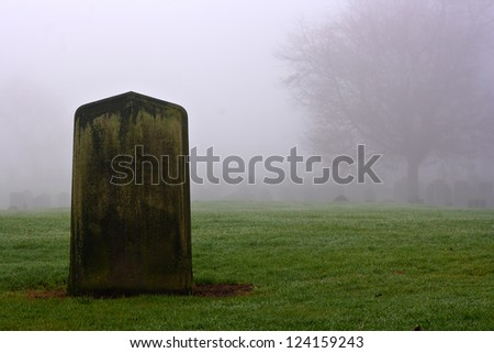 Single gravestone in a spooky graveyard on a foggy day - stock photo
