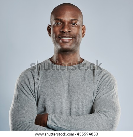 Single handsome black man with folded arms, confident expression and pleasant smile in gray compression shirt over neutral background - stock photo