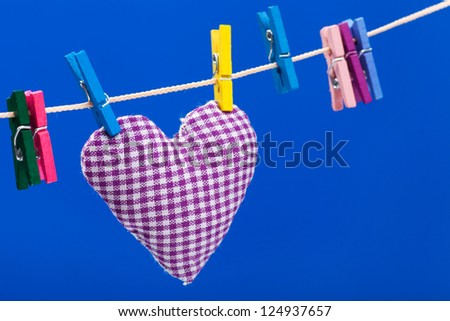 single heart on clothesline with clothespins, blue background - stock photo