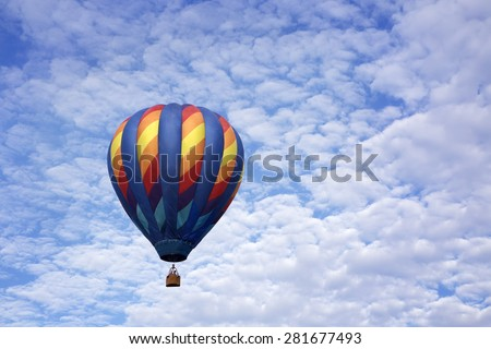 Single hot air balloon floating up into a blue sky full of white fluffy clouds - stock photo