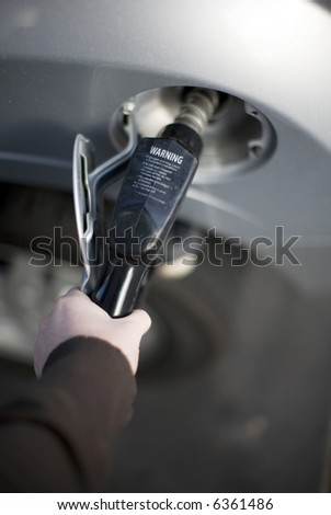 Single human hand holding fuel pump while in gas tank - stock photo
