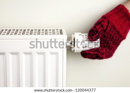 Single human hand with knitted glove turning radiator thermostat - stock photo