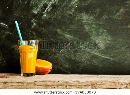 Single large glass full of mango fruit smoothie on wooden table with copy space over chalkboard black background - stock photo