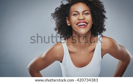 Single laughing young adult woman in sleeveless undershirt and soft frizzy hair leaning forward over gray background and copy space - stock photo