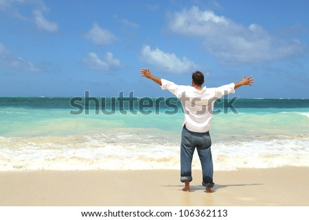 single male standing on beach facing ocean with arms wide open to the sky - stock photo