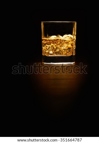 Single Malt Whiskey in a glass on a wooden table top with space for text, portrait. - stock photo